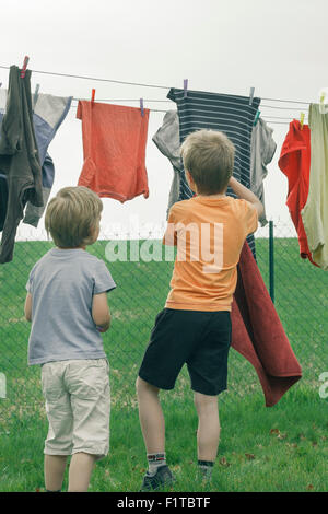 Two young boys hanging laundry on a clothesline. - Stock Photo