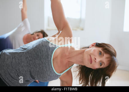 Portrait of mature woman doing stretches in a gym. Fitness trainer with student in background doing Ardha Chandrasana. - Stock Photo