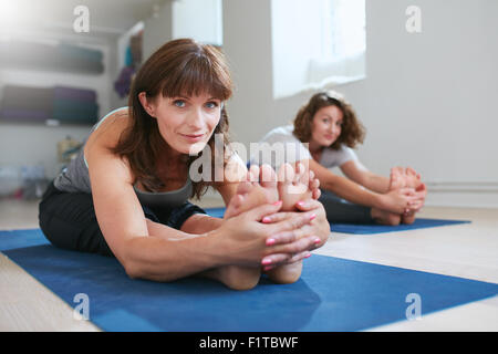 Women doing yoga together at gym, practicing paschimottanasana pose. Fitness female seated forward bend pose during - Stock Photo