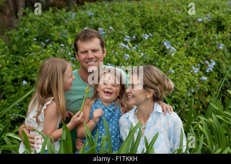 Family of four among green plants - Stock Photo