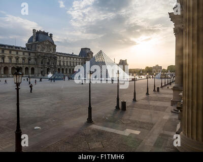 The Louvre Museum Pyramid at sunset . The huge wings of the Louvre Palace surround the new Pyramid entrance at sunset. - Stock Photo