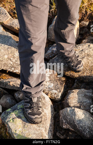 hiker standing on rocks - Stock Photo