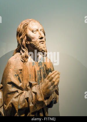 Medieval Wooden sculpture of Christ Praying. A worn statue of a praying Christ figure, its paint flaking off to - Stock Photo