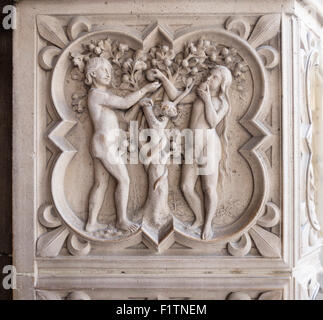 Relief carving of Adam, Eve and the Tree of Knowledge. Eve eats an apple with Adam looking on with a serpent - Stock Photo