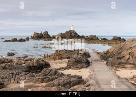 La Corbiere Lighthouse, Jersey  viewed from the mainland while tide going out - Stock Photo