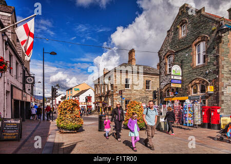 Tourists strolling in Keswick High Street on a sunny autumn day, Cumbria, England. - Stock Photo