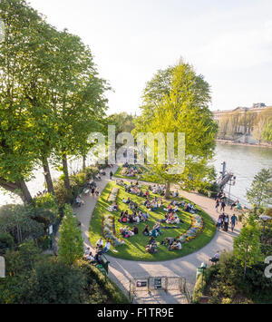 Park at the tip in the Seine . Tourists and locals enjoy the evening sunshine at the tip of the Île de la Cité in - Stock Photo
