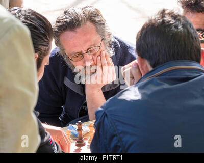 Garden Chess Game. Head in hand, Parisians concentrate play chess in the Jardin du Luxembourg. - Stock Photo