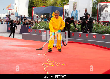 Workers remove rain water from the red carpet before the gala screening for the film The Danish Girl  at the 72nd - Stock Photo