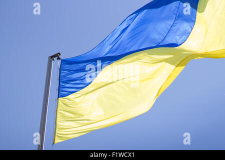 Blue and yellow national flag of Ukraine waving on blue sky - Stock Photo