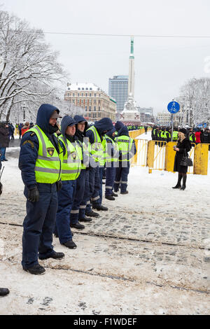 RIGA, LATVIA, MARCH 16, 2010: Local police guard cordon behind crowd control barriers at the Freedom Monument at - Stock Photo