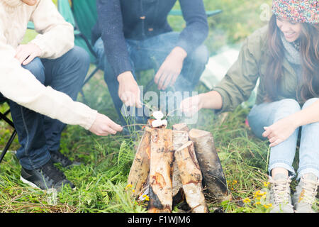close up of hikers roasting marshmallow on fire - Stock Photo
