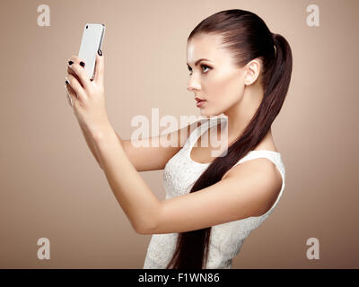 Beautiful young woman taking selfie. Girl photographing herself with phone. Beauty fashion. Eyelashes. Cosmetic - Stock Photo