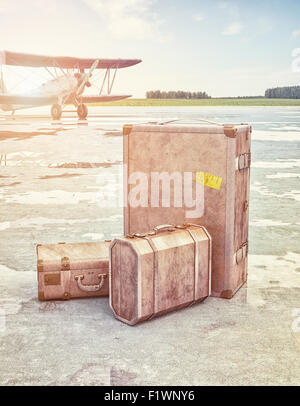 Vintage suitcases and retro airplane on runway. 3d concept - Stock Photo