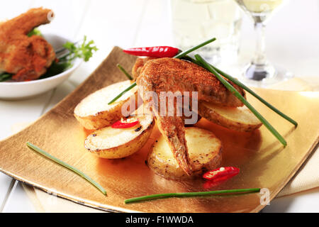 Spicy chicken wing and pan fried potatoes - Stock Photo