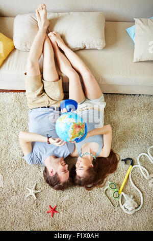 Young man and woman with globe looking at one another while lying on the floor and making plans for summer - Stock Photo