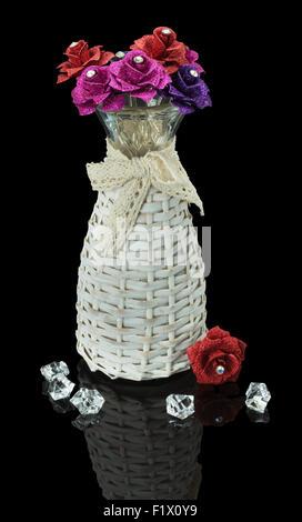 artificial roses in vase isolated on the black background. - Stock Photo