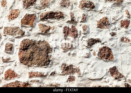 Fragment of a natural old stone wall as background - Stock Photo