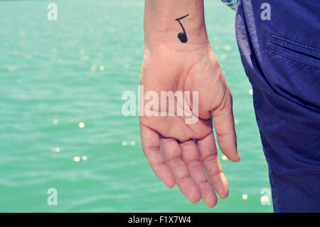 closeup of a young caucasian man seen from behind with a musical note painted in his wrist - Stock Photo