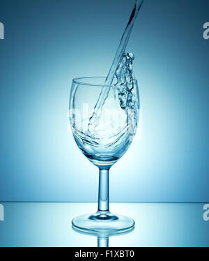 white wine pouring on blue background. - Stock Photo