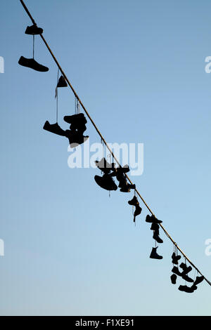 Pairs of shoes hanging from on a wire in Prague, Czech Republic - Stock Photo