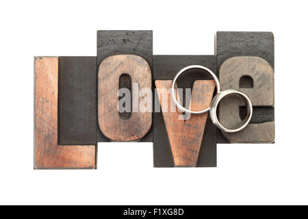 wedding rings upon the word love, written with vintage letterpress printing blocks, isolated on white background - Stock Photo