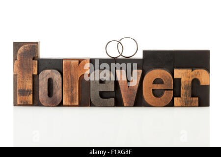 wedding rings upon the word forever, written with vintage letterpress printing blocks - Stock Photo