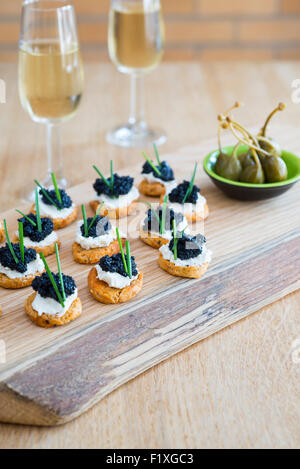 Canapes made from crostini with soft cheese and seaweed 'caviar'. - Stock Photo