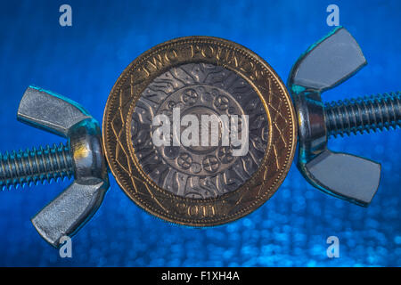 Concept of turn the screw, pressurize, press. Macro-photo of UK £2 coin being squeezed between two wing nuts. Metaphor - Stock Photo