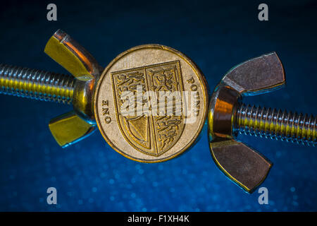 Concept of turn the screw, pressurize, press. Macro-photo of UK £1 coin being squeezed between two wing nuts. Metaphor - Stock Photo