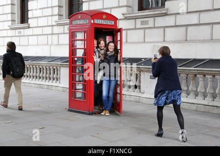 A family group of tourists squeeze into a traditional red English telephone box or kiosk to grab a memorable photo - Stock Photo