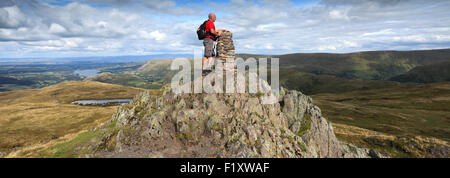 Walker at the Summit cairn and OS Trig Point on Place Fell, Lake District National Park, Cumbria, England, UK. - Stock Photo