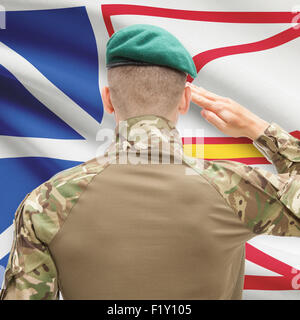 Soldier saluting to Canadial province flag series - Newfoundland and Labrador - Stock Photo