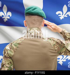 Soldier saluting to Canadial province flag series - Quebec - Stock Photo