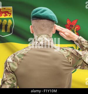 Soldier saluting to Canadial province flag series - Saskatchewan - Stock Photo
