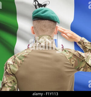 Soldier saluting to Canadial province flag series - Yukon - Stock Photo