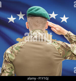 Soldier in hat facing national flag series - Kosovo - Stock Photo