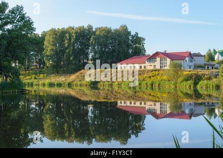 New brick house on the lake (pond) - Stock Photo