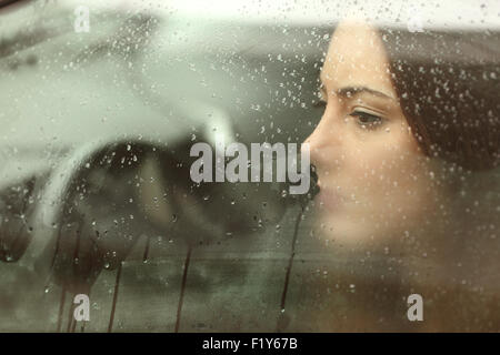Sad woman or teenager girl looking through a steamy car window - Stock Photo