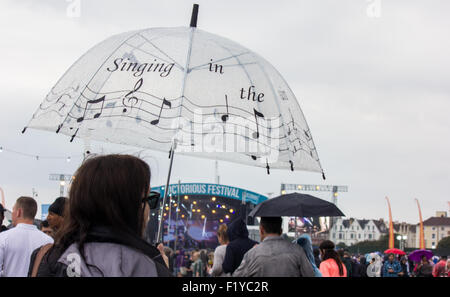 Someone holding an umbrella up reading the words 'Singing in the rain' at Victorious Festival 2015 with main stage - Stock Photo