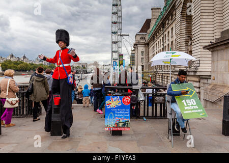 A Man Dressed In A Guards Uniform Hands Out Leaflets and Poses For Photographs With Tourists, London, England - Stock Photo