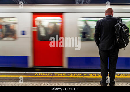 A Business Man In A Suit Waits For A Train, The London Underground, London, England - Stock Photo