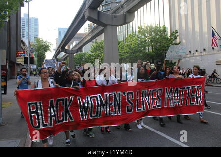 Members of the black lives matter movement carry a gender specific banner while marching down 5th ave in downtown - Stock Photo