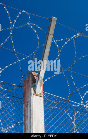 Prison concrete pillar and barbed wire fence against blue sky, security concept - Stock Photo
