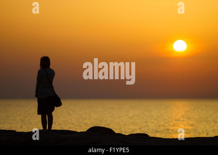 Sunset silhouette of young girl waiting for someone on seaside - Stock Photo