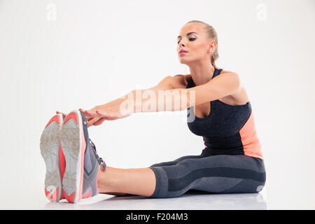 Portrait of a fitness woman stretching legs isolated on a white background - Stock Photo
