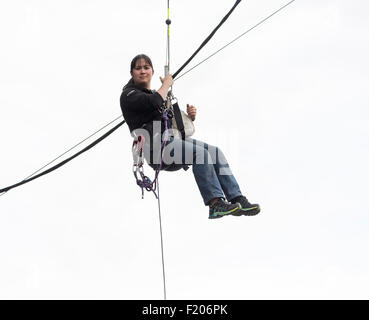 Young woman with a calm expression hangs dangling from a rope in a harness with safety equipment - Stock Photo