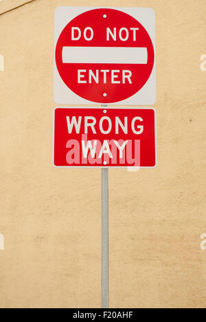 California, USA. 'Do Not Enter' and 'Wrong Way' road signs in white writing on red background. - Stock Photo