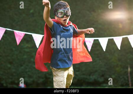 Boy wearing goggles and cape in superhero stance - Stock Photo