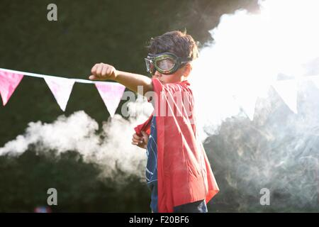 Boy wearing goggles and cape in superhero stance in front of smoke cloud - Stock Photo